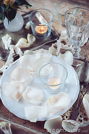 Vintage table setting with rose petals