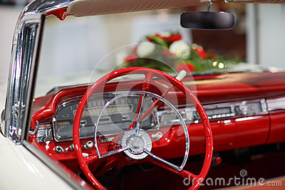 Vintage wedding car in red with bride flower bouquet
