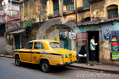 Vintage yellow taxi car stopped at the old street