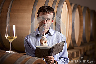 Vintner in cellar analyzing white wine.