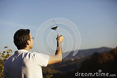 Vintner checking wine.