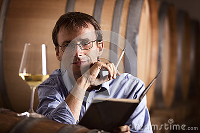 Vintner looking at glass of white wine in cellar.