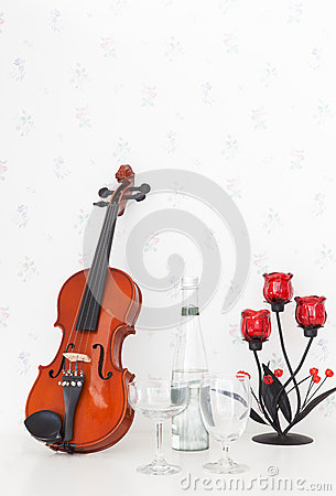 Violin and wine glass on white table