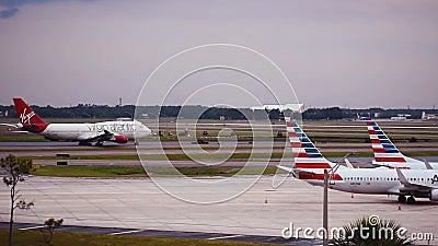 Virgin Atlantic samolotowy szybownictwo na częściowym widoku American Airlines samoloty przy Orlando lotniskiem międzynarodowym i zbiory