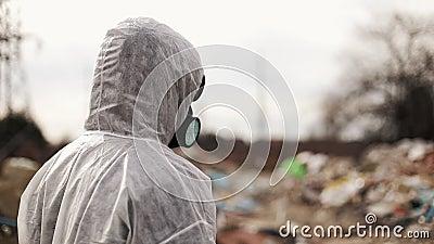 Virologemann in der schützenden Kostüm- und RespiratorGasmaske gehend nahe Deponiegeländeverschmutzung, Umweltkatastrophe stock footage