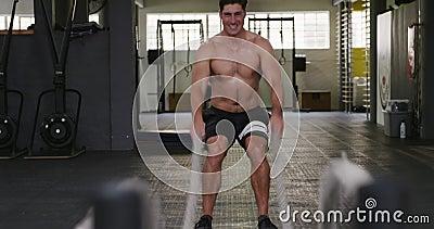 Visão frontal de um homem atlético caucasiano trabalhando com cordas de batalha vídeos de arquivo
