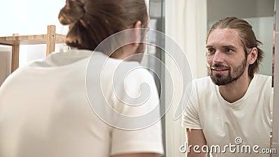 Visage de lavage d'homme avec de l'eau l'eau propre et regarder le miroir banque de vidéos
