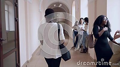 Visión desde la parte posterior del estudiante que pasa solamente a través del pasillo almacen de video