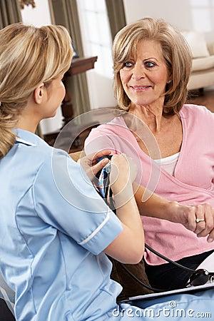 Visitante de la salud que toma la presión arterial de la mujer