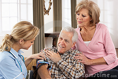 Visitante de la salud que toma la presión arterial del hombre mayor