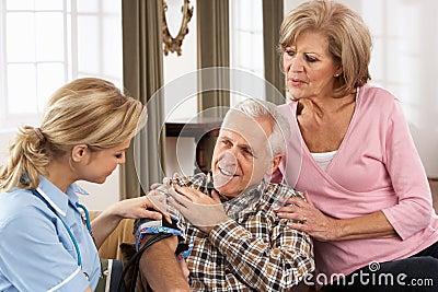 Visiteur de santé prenant la tension artérielle d homme aîné