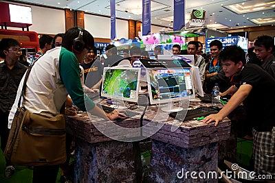 Visiteurs jouant des jeux vidéo à l exposition 2013 de jeu d Indo Image stock éditorial