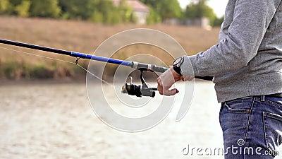 Visserij op het meer Een man was aan het vissen op een staaf De man haalt de vis uit het meer Vis aan de haak stock videobeelden