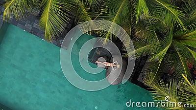 Vista aérea de aviões aéreos não tripulados de uma jovem fina em beige bikini e palha que relaxa na piscina de luxo Férias video estoque