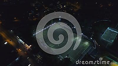 Vista aérea de los pájaros del campo de fútbol durante un partido iluminado por la noche en los deportes almacen de metraje de vídeo