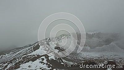 Vista aérea del cráter de un pico Viejo del volcán en Tenerife, cubierto con nieve y nubes metrajes