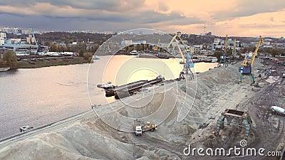 Vista aérea do carregamento de granéis de guindaste pesado no terminal portuário de carga do rio Dnieper em Kiev, à noite, à hora vídeos de arquivo