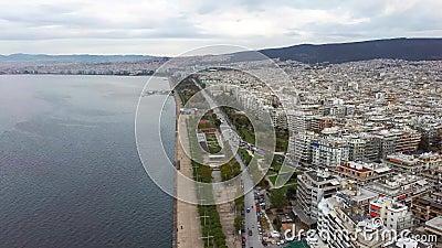 Vista aérea do litoral urbano na cidade de Salónica, edifícios e parques, céu nublado, inverno, movimento lateral por drone vídeos de arquivo