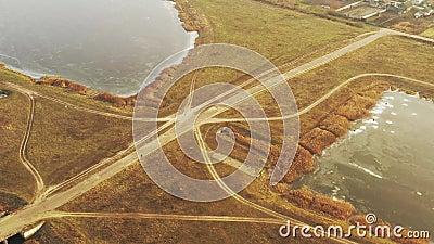 Vista aérea Homem andando de bicicleta na estrada rural perto de lagos no final do outono modo de exibição de drone Vista visual  filme