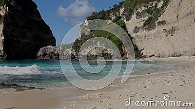 Vista da praia tropical selvagem com areia branca e ondas com espuma de oceano turquesa e rochas marinhas e penhasco sobre fundo vídeos de arquivo