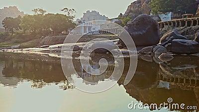 Vista dal fiume calmo alla vecchia bella città indiana sulla Banca piana