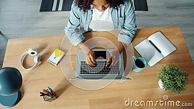 Vista dall'alto di una donna afro-americana che lavora con il computer portatile all'interno della casa dattilografa stock footage