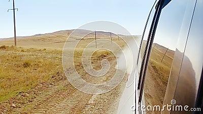 Vista dall'automobile commovente della finestra sulla strada rurale polverosa con i campi e le colline del deserto stock footage