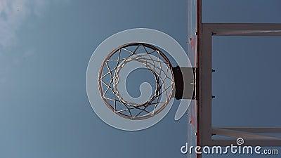 Vista de ángulo bajo de puntuación en cesta en movimiento lento contra fondo del cielo azul. Estilo de vida saludable y deporte almacen de video