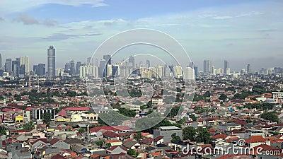 Vista de casas pequenas e de arranha-céus atrás deles em Jakarta, Indonésia filme