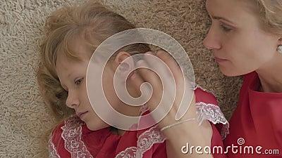 Vista de cima de uma jovem beijando o ombro da garotinha Mãe e filha vestidos de roupas vermelhas, deitados no macio video estoque