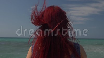 Vista de la parte posterior de una mujer con el pelo rojo que vuela en el viento contra el contexto de la resaca del mar metrajes