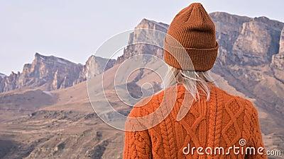 Vista de trás uma viajante de suéter laranja e um chapéu em uma banca ao ar livre contra o pano de fundo do épico video estoque