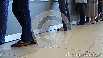 Vista delle gambe dei clienti in piedi negli uffici moderni, serviti in banca Media Le persone sono in coda per archivi video