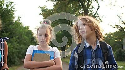 Vista frontal. Três estudantes vão à escola na vila em uma estrada rural. Estudo na Europa Oriental, de volta à escola video estoque