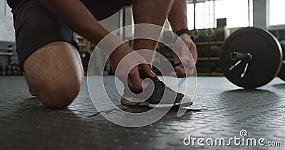 Vista frontale bassa di un atletico caucasico che si allaccia le scarpe video d archivio