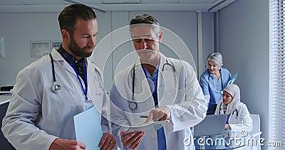 Vista frontale dei medici uomini caucasici che discutono sul tablet digitale all'ospedale archivi video