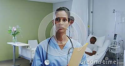 Vista frontale della dottoressa afro-americana che guarda la telecamera nel reparto dell'ospedale stock footage