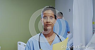 Vista frontale della dottoressa afro-americana che guarda la telecamera nel reparto dell'ospedale video d archivio