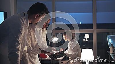 Vista lateral de dos ingenieros de desarrollo de electrónica que hablan del tablero electrónico y que explican los detalles de su almacen de metraje de vídeo