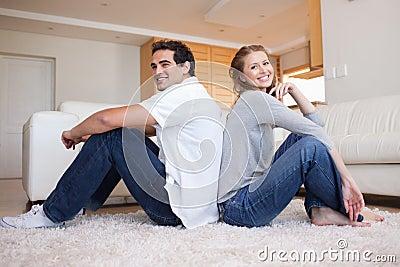 Vista lateral de los pares jovenes que se sientan en el suelo adosado mutuamente
