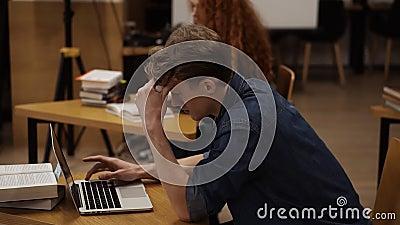 Vista lateral de um jovem focado usando laptop na biblioteca Estudante europeu bonito que estuda em público ou universitário video estoque