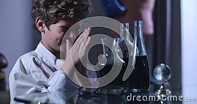 Vista lateral de un extraño niño caucásico que se frota las manos y mira los frascos con líquidos Joven genio malo trabajando almacen de metraje de vídeo