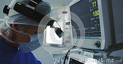 Vista lateral de una doctora caucásica que trabaja en un monitor médico en el quirófano del hospital almacen de video