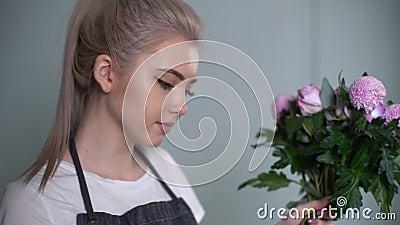 Vista lateral de una joven florista rubia vistiendo delantal haciendo ramo floral metrajes