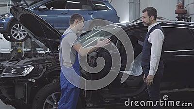 Vista lateral del joven mecánico caucásico sacudiendo la mano del cliente frente al automóvil roto Empresario barbudo almacen de video