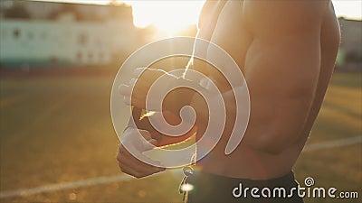 Vista laterale ravvicinata di uno sportivo muscolare che mette il polso nero sulle mani Sole luminoso sullo sfondo video d archivio
