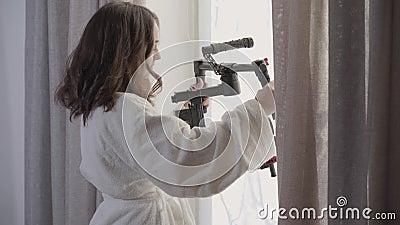 Vista laterale ritratto di una giovane donna di bruna caucasica in piedi davanti alla finestra con un'apparecchiatura video Belli video d archivio
