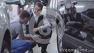 Vista a metà strada del giovane meccanico caucasico seduto con un cliente a caccia di auto professionista stock footage