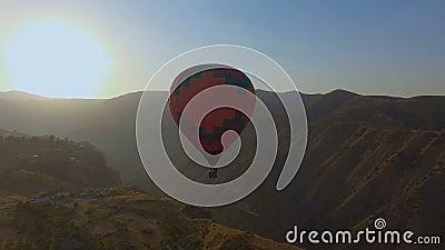 Vista panorámica del vuelo del globo del aire caliente a través del cielo en paisaje de la montaña almacen de video