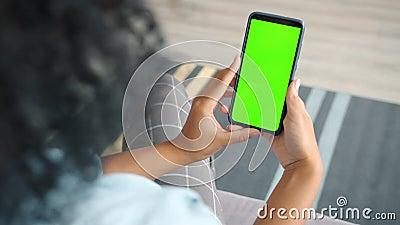 Vista posterior de la morena que contiene la llave de croma pantalla verde para ver el contenido del smartphone almacen de video